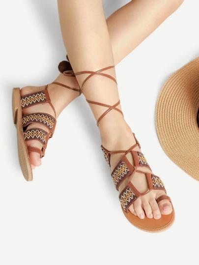 Sandalias planas anudadas a la pierna con detalle de pompones